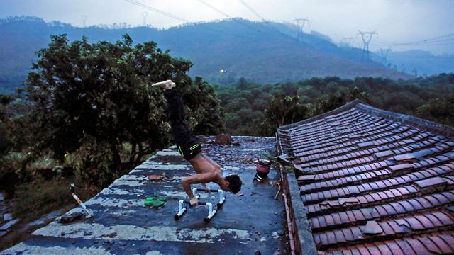 Shi Shenwei, demuestra su rutina de entrenamiento en el tejado de una casa antigua, en el pueblo de Huangshan, cerca de Quanzhou, provincia de Fujian, China