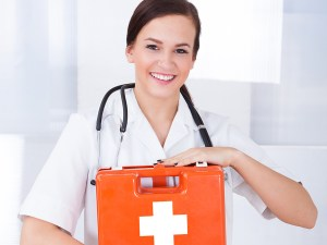 Portrait of happy young female doctor holding first aid box in hospital