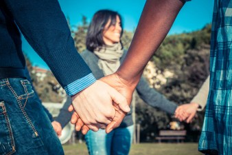 25188962 - multiracial young people holding hands in a circle