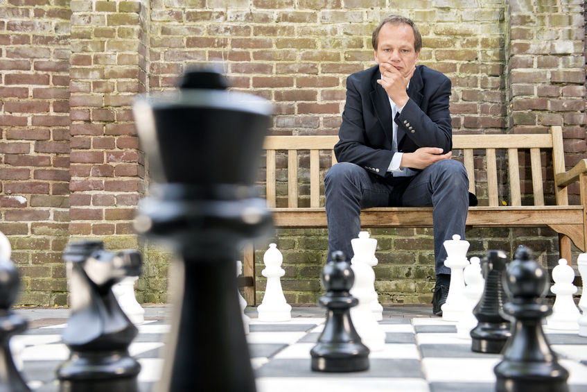 41411270 - concentrated man, thinking strategically about his next move, sitting on a wooden bench in front of a brick wall during an outdoor chess game using life sized chess pieces and chess board