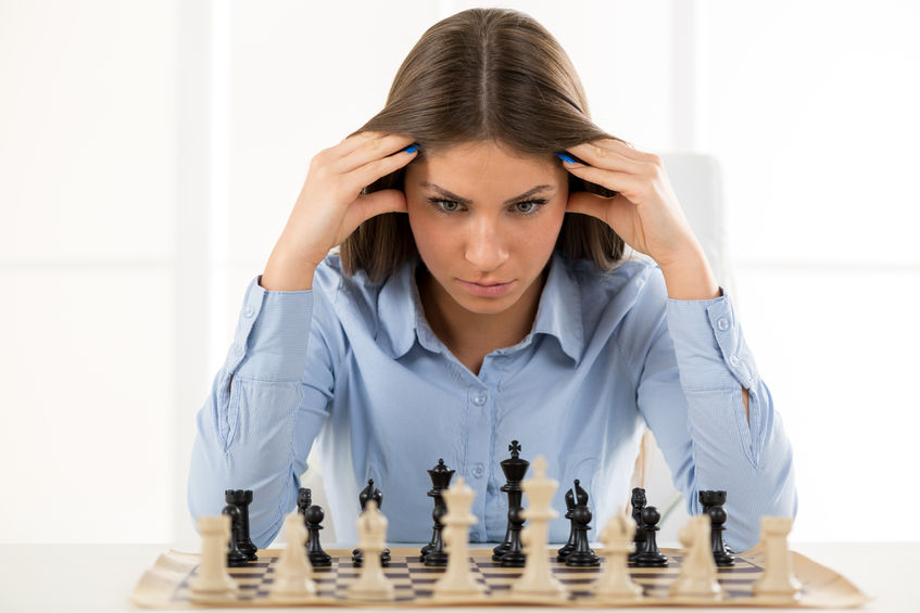 A young businesswoman is sitting in front of a chess board and thinking staring at the figure, holding hands on her head.