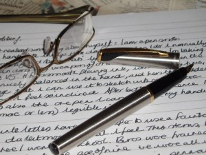 written page with glasses and pen