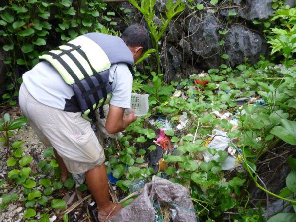 Mang Jun picks up trash entangled in beach plants