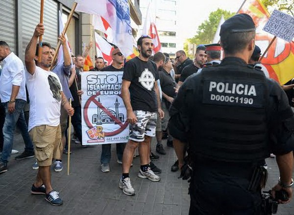 Police officers stand guard during a demonstration by members of the Spanish right-wing group Falange on the Rambla on August 18, 2017, a day after a van ploughed into the crowd, killing 14 persons and injuring over 100 on the Rambla in Barcelona. Drivers have ploughed on August 17, 2017 into pedestrians in two quick-succession, separate attacks in Barcelona and another popular Spanish seaside city, leaving 14 people dead and injuring more than 100 others. Some eight hours later in Cambrils, a city 120 kilometres south of Barcelona, an Audi A3 car rammed into pedestrians, injuring six civilians -- one of them critical -- and a police officer, authorities said. / AFP PHOTO / JOSEP LAGO