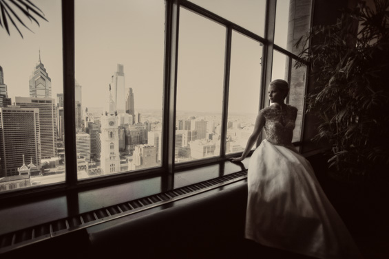 bride looking out Lowes Hotel window at Philadelphia - Crystal Tea Room Wedding - photo: Daniel Fugaciu Photography | via http://emmalinebride.com