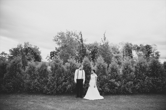 bride and groom - b & w image - standing in front of woods.  groom in suspenders with bow tie - photo: michelle gardella photography