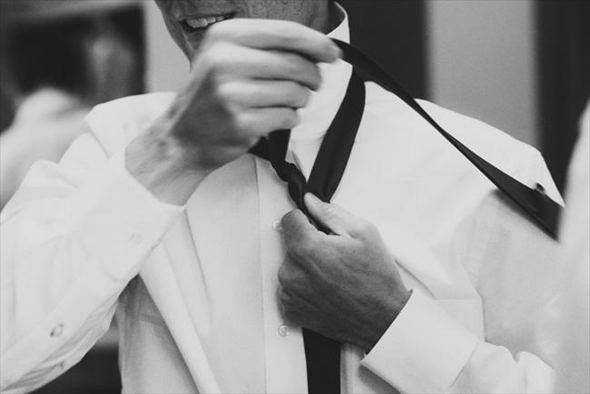 The groom putting on his tie | Photo: Searching for the Light Photography LLC | via http://emmalinebride.com/real-weddings/colorado-chic-wedding-kendall-brian/