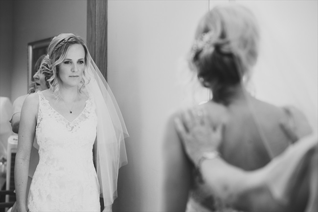 The bride looks in the mirror before the ceremony | Photo: Searching for the Light Photography LLC | via http://emmalinebride.com/real-weddings/colorado-chic-wedding-kendall-brian/