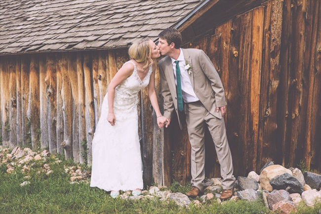 The bride and groom kiss in front of the barn | Photo: Searching for the Light Photography LLC | via http://emmalinebride.com/real-weddings/colorado-chic-wedding-kendall-brian/