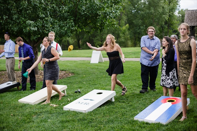 Guests played cornhole as entertainment before dinner | Photo: Searching for the Light Photography LLC | via http://emmalinebride.com/real-weddings/colorado-chic-wedding-kendall-brian/