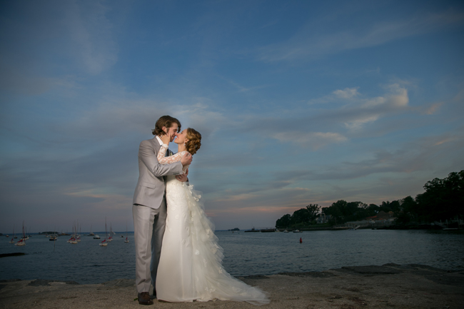 bride and groom kiss in Greenwich Harbor at Connecticut wedding - photo: Melani Lust Photography | via http://emmalinebride.com