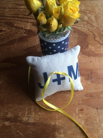 ring bearer pillow with initials blue text and yellow ribbon