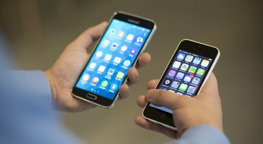 A Samsung Electronics Co. Galaxy S5 smartphone, left, and Apple Inc. iPhone 5c are held for a photograph in Hong Kong, China, on Wednesday, May 14, 2014. Apple and Samsung are the world's top two smartphone vendors, according to the International Data Corp., which expects global shipments to reach 1.2 billion smartphones this year, from 1 billion last year. Photographer: Brent Lewin/Bloomberg