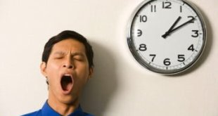 Close-up of a businessman yawning near a wall clock --- Image by © asiaselects/Corbis