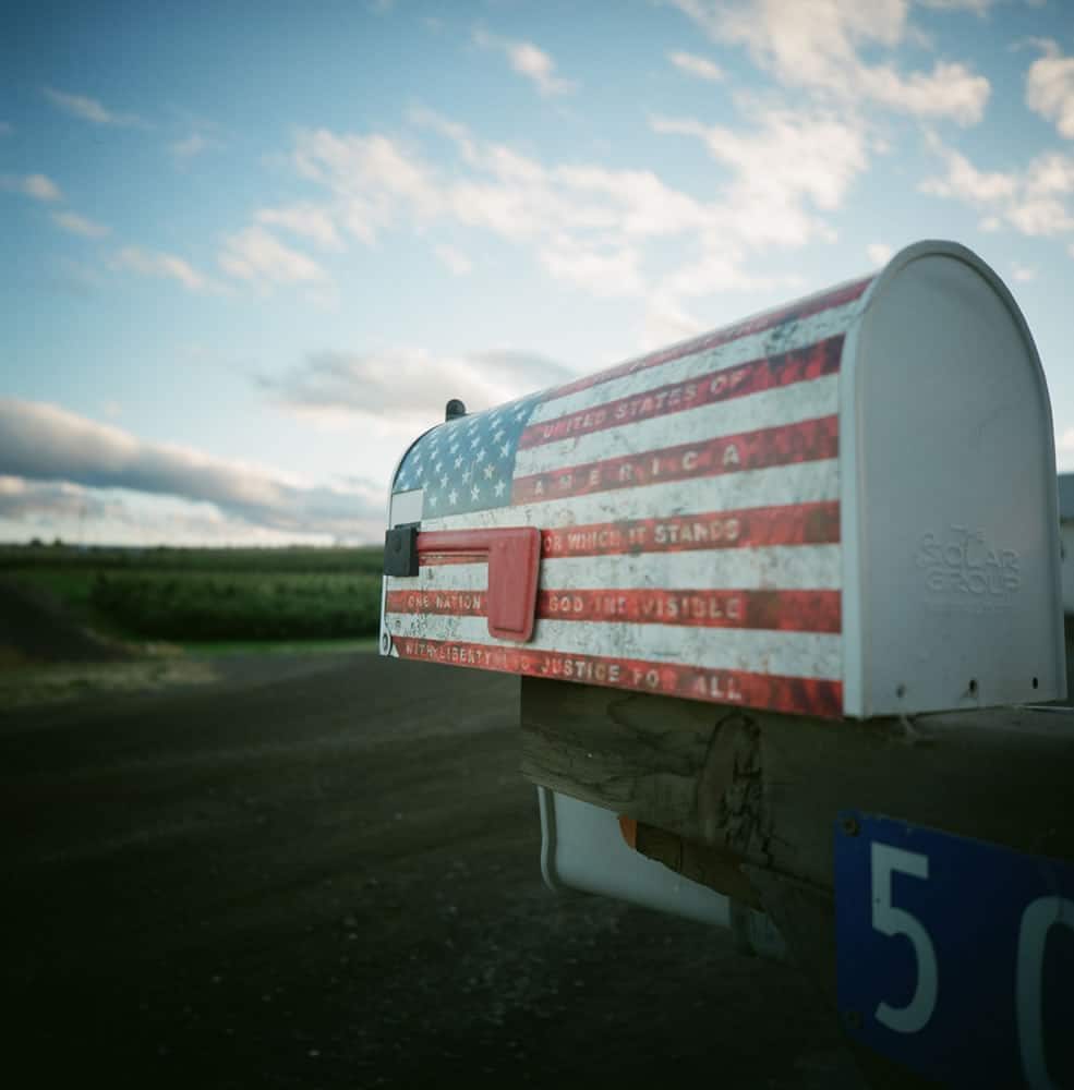 A close-up of a mailbox outside the little town of Tieton, WA, with apple orchards in the background.