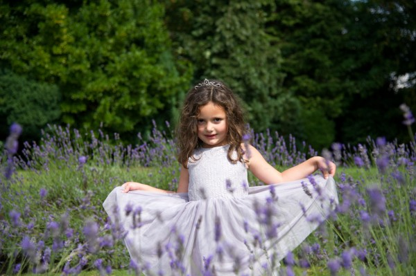 Small girl in lavender dress behind the lavender