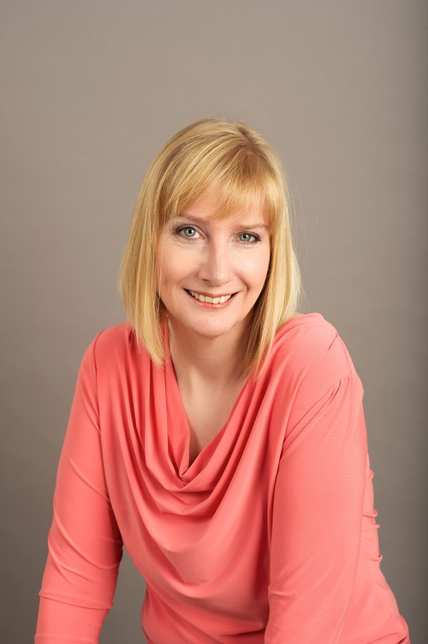 Lady in peach top with blond hair, posing for a studio business portrait