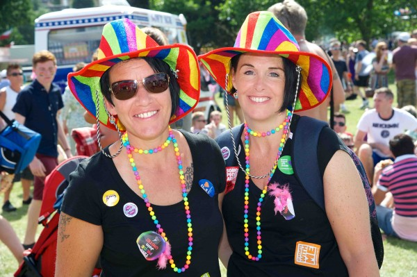 Two ladies in rainbow hats and coloured beads at Pride