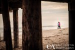Engaged couple kiss below the Capitola Warf. Capitola CA