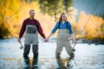 Couples portrait suited up for an evening on the river. Waders & fly rods in hand.