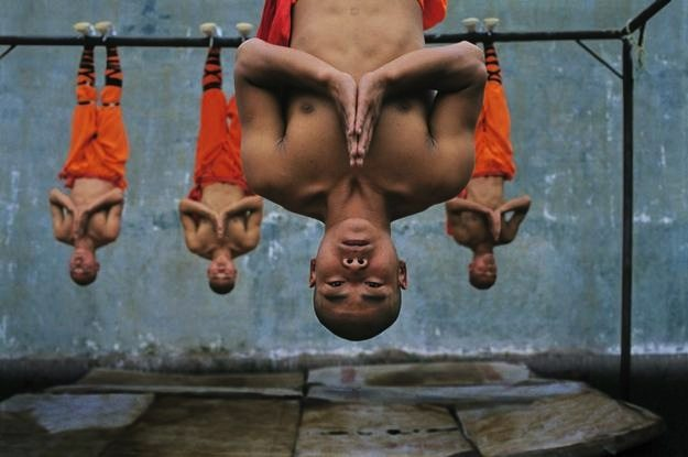 Steve McCurry. Note the orange of the monk's skin and clothes juxtaposed against the faint blue of the background