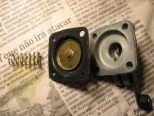 O diafragma injetor, entre sua mola e sua tampa, demonstrando a ordem correta de montagem. O diafragma injetor bombeia combustível para o giclê de aceleração sempre que o acelerador é comprimido.