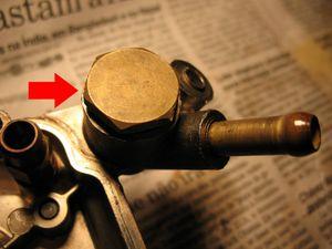"""Visão da entrada de combustível. Retire esse parafuso sextavado com uma chave 19 mm (3/4"""")."""