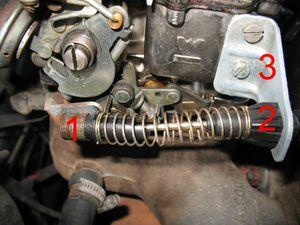 Do lado esquerdo, solte o cabo do acelerador.   Primeiro, deslize a peça de metal (1) para trás, e solte a ponta do cabo. Depois, pressione simultaneamente os quatro lados da região indicada (2). Deslize o cabo pelo suporte metálico do carburador (3).