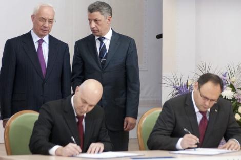 El primer ministro de Ucrania, Mykola Azarov (de pie a la izq.) mientras el falso representante, Jordi Sardà Bonvehi (sentado, izq.), firmaba el acuerdo. | Reuters