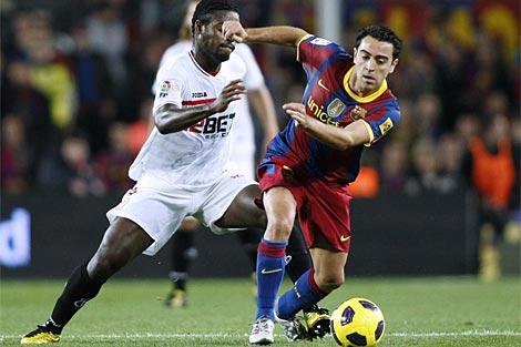 Xavi elude a Romaric, en un momento del Barcelona-Sevilla. (AFP)