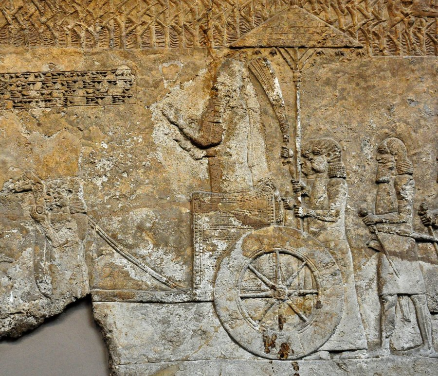 This bas-relief is part of a series of reliefs which depict the formation and transport of a colossal winged-bull (Lamassu) for the palace of the Assyrian king Sennacherib. In this relief, the king stands in a rickshaw (a royal chariot which pulled by two servants) and he watches the progress of the work. A servant fans the king and another one holds a sunshade over the king's head. From court VI, probably panel 60 of the South-West palace at Nineveh (modern Mosul Governorate, Iraq), northern Mesopotamia. Neo-Assyrian period, 700-692 BCE. (The British Museum, London).