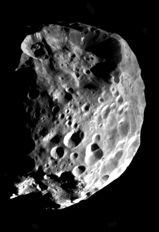 A lua Phoebe (Febe) fotografada pela sonda Cassini é negra como o carvão e realiza uma órbita retrógrada