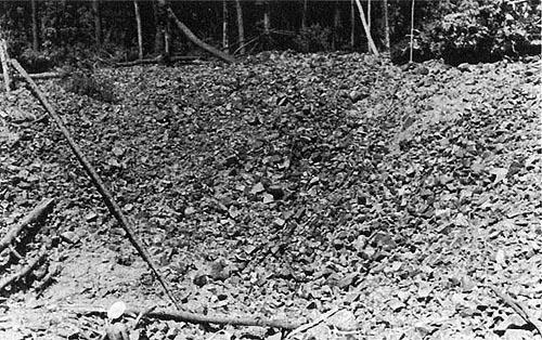 A maior cratera encontrada em Sikhote Alin com ~27 metros de diâmetro. Repare no homem na parte de baixo da foto. Este é o evento mais recente catalogado no banco de dados de impactos. Note a figura humana na borda inferior da imagem.