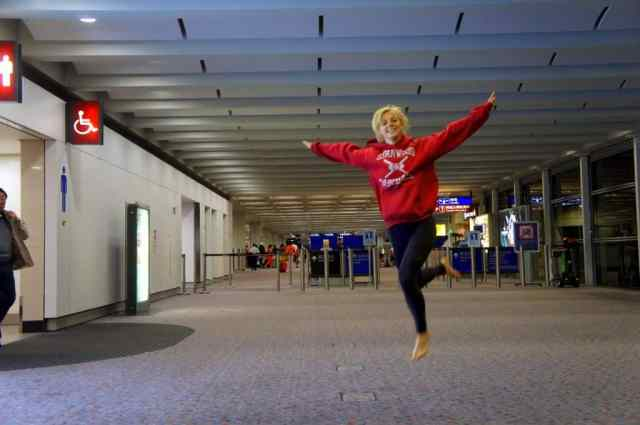 A girl with no shoes jumping at Hong Kong airport