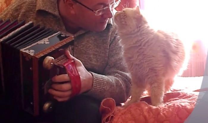 アコーディオンを演奏する飼い主さんと猫