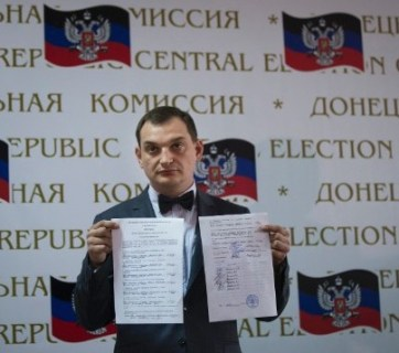 Co-chairman of the Presidium of the People's Republic of Donetsk and vote-counter Roman Lyagin shows documents with the results of the referendum to journalists at a news conference in Donetsk, Ukraine, Monday, May 12, 2014, with Donetsk republic signs in the background. The balloting Sunday in the Donetsk and Luhansk regions_ which together have 6.5 million people _ was condemned as a sham and a violation of international law by Kiev's interim government and the West. (AP Photo/Alexander Zemlianichenko)