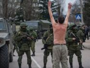 A Ukrainian man stands in protest in front of unmarked Russian soldiers in the Crimea