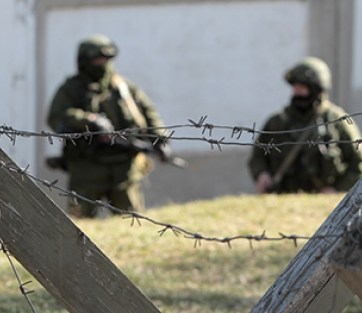 Russian soldiers behind a razor-wire barrier