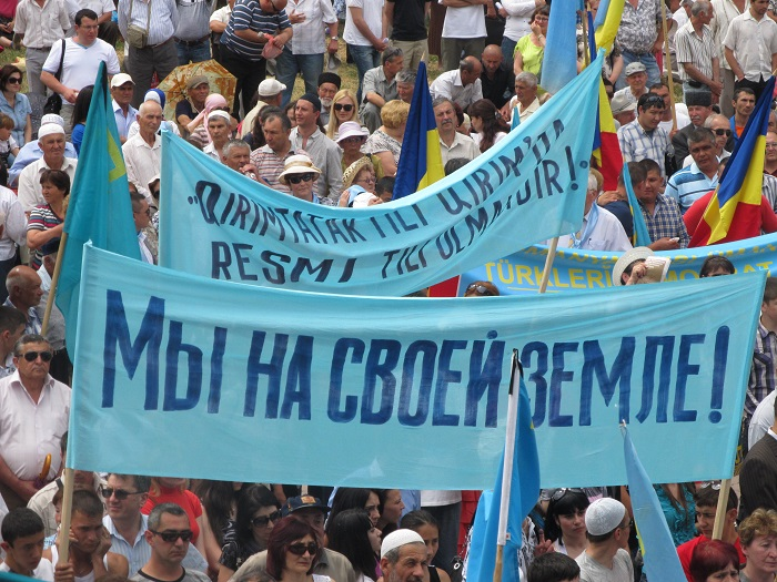 "Crimean Tatar protest. The sign in Russian reads: ""We are on our own land!"""