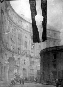 "Flag of Hungary, with the communist coat of arms cut out. The flag with a hole became the symbol of the revolution. Budapest, 1956 (Photographed at the ""Corvin köz"")"