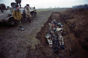Russian soldiers next to a mass grave with Chechen militia and civilians during the Second Russian-Chechen War. Note the rope used to drag corpses behind the army vehicles from the place of killing to the grave (Image: Natalia Medvedeva, wikipedia.org)