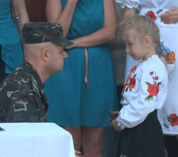"The daughter of a Ukrainian soldier from Zhytomyr receives an Order ""For Courage"" awarded to him posthumously, June 2015. (Photo: zhitomir.info)"