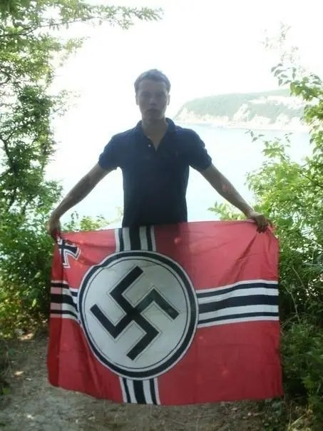 Russian neo-Nazi Alexey Milchakov with a Nazist swastika flag (Image: Milchakov's social network page)