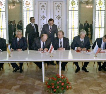 "Signing the Agreement to eliminate the USSR and establish the Commonwealth of Independent States. Ukrainian President Leonid Kravchuk (second from left seated), Chairman of the Supreme Council of the Republic of Belarus Stanislav Shushkevich (third from left seated) and Russian President Boris Yeltsin (second from right seated) during the signing ceremony to eliminate the USSR and establish the Commonwealth of Independent States. Viskuly Government Retreat in the Belarusian National Park ""Belovezhskaya Pushcha"". (Image: U. Ivanov, RIAN archives via Wikipedia)"