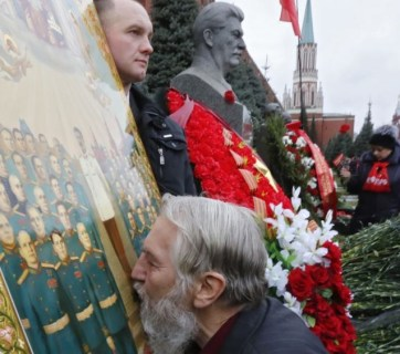 A man kisses an icon of Soviet dictator Joseph Stalin next to his grave in front of the Kremlin wall in Moscow.
