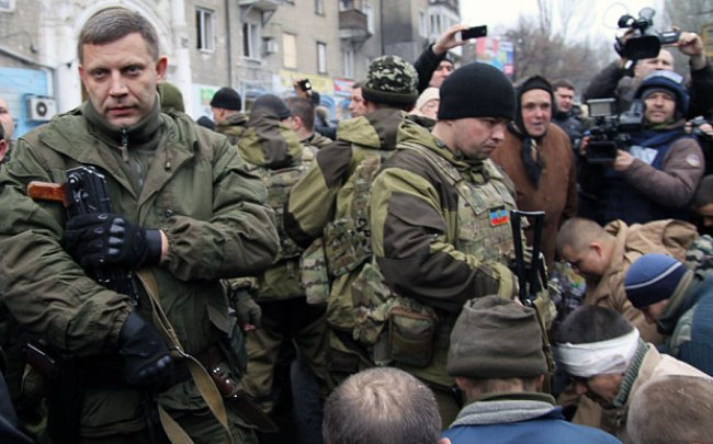 Leader of the self-declared Donetsk People's Republic Alexander Zakharchenko stands next to kneeling captive Ukrainian soldiers
