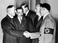 Hands clasped in friendship, Adolf Hitler and England's Prime Minister Neville Chamberlain, are shown in this historic pose at Munich on Sept. 30, 1938. This was the day when the premier of France and England signed the Munich agreement, sealing the fate of Czechoslovakia. Next to Chamberlain is Sir Neville Henderson, British Ambassador to Germany. Paul Schmidt, an interpreter, stands next to Hitler. (Image: AP)