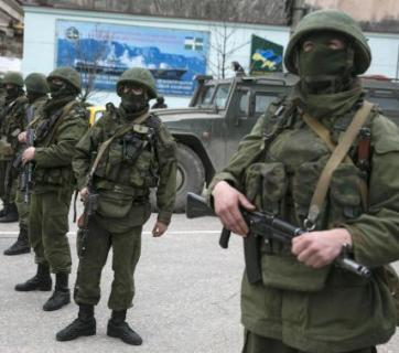 Masked Russian servicemen stand near their army vehicles blockading a Ukrainian border guard base in the Crimean town of Balaclava. March 2014