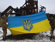 "The ""Shakhta Butivka"" Ukrainian position west of Donetsk. Soldiers hold up the flag saved from the ruins of the poppethead destroyed by artillery fire from Donetsk on February 26.  Credit: mil.gov.ua"