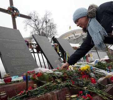 A woman brings flowers to a monument to the killed protesters at Euromaidan. Photo: Alya Shandra
